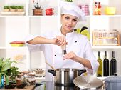foto of chef cap  - Young woman chef cooking in kitchen - JPG