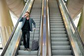 picture of escalator  - Horizontal portrait of a business man talking on the phone while going down escalator - JPG