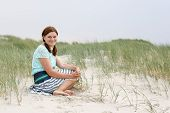 Young Happy Girl Relaxing On Sand Dunes Of The Beach Of St.peter Ording