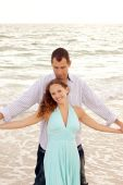Beautiful Happy Young Adult Couple At The Ocean With Arms Outstretched