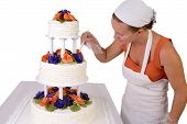 pic of sugar paste  - baker lady with a white bandanna giving to a wedding cake final touchups cake has fondant ruffles on the side and decorated with orange and purple gum paste roses - JPG