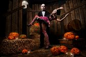 stock photo of dracula  - Portrait of a man and sexy woman vampires with halloween pumpkin against wooden background - JPG