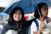 BANAUE, PHILIPPINES, DECEMBER 03:Two Filipina girls sheltering under an umbrella together as they wa