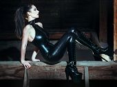 stock photo of woman boots  - Sexy dominatrix at night posing on timber bdsm - JPG