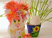 stock photo of paint pot  - Children hack cardboard lion standing next to the egg and a pot of seedlings - JPG
