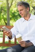 Businessman using mobile phone while holding disposable coffee cup at park