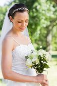 Beautiful shy bride holding flower bouquet in garden