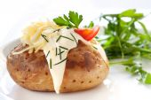 picture of baked potato  - Baked potato filled with sour cream and grated cheese with arugula on the side - JPG