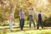 Family Throwing Autumn Leaves In The Air