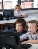Little schoolchildren looking at computer monitor in lab