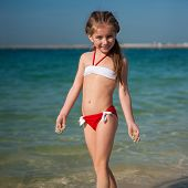 cute little girl in red-and-white swimsuit on the beach