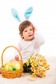 stock photo of ester  - Ester bunny baby with basket with eggs and flowers sitting on carpet - JPG