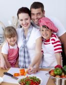 picture of family fun  - Happy Family Cutting Colourful Vegetables In Kitchen - JPG