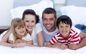 pic of happy family  - Smiling happy family lying in bed together - JPG