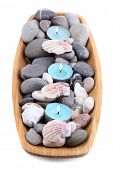 Wooden bowl with Spa stones, sea shells and candles isolated on white