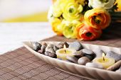 Spa stones and candle in decorative bowl, on bamboo mat, on color wooden table, on bright background