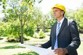 Confident businessman looking away while holding blueprint in park