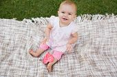 High angle portrait of a cute baby with heart shaped lollipop sitting on blanket at the park