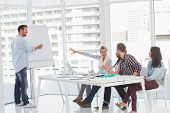 stock photo of presenter  - Man presenting an idea to his colleagues in creative office - JPG