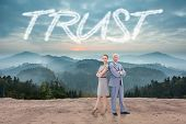 The word trust and serious businessman standing back to back with a woman against scenic countryside