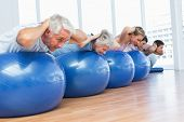 Sporty people stretching on exercise balls in the bright gym
