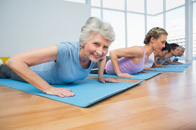 foto of senior class  - Fitness group doing cobra pose in row at the yoga class - JPG