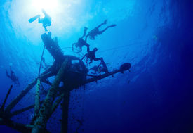 stock photo of bottomless  - Group of divers exploring ship wreck in the tropical sea - JPG