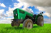 picture of tractor  - Green tractor in the field with a cloudy sky - JPG