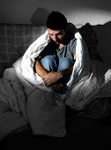image of grieving  - Young man sitting on couch at home wearing jeans wrapped in messy duvet suffering depression and emotional crisis grieving in solitude and feeling lonely and desperate in dim light - JPG