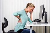 picture of spinal column  - a woman sitting at a desk and has pain in the back - JPG