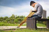 stock photo of amputation  - Injured Man with crutches sitting on a bench - JPG