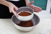 foto of flour sifter  - Woman sifting cocoa powder into a metal bowl with a flour sifter - JPG