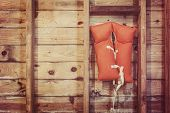 picture of life-boat  - Old orange life jacket hanging in a boat house - JPG