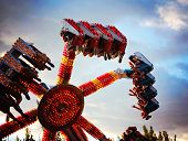 stock photo of carnival ride  - a fair ride during dusk on a warm summer evening - JPG