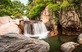 stock photo of tourist-spot  - The tourists in China Qingdao laoshan scenic spot the cascades - JPG