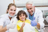 stock photo of pediatric  - Pediatric dentist assistant and little boy all smiling at camera with thumbs up at the dental clinic - JPG