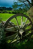 stock photo of quaint  - old wagon wheel leaning on a fence in a quaint traditional style farm - JPG