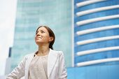 stock photo of self-confident  - Portrait of happy and self confident latina businesswoman in tailleur looking confident at skyscraper and office buildings in the city - JPG