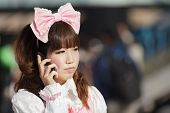 stock photo of lolita  - Japanese lolita cosplay woman using her mobile phone in a Tokyo street - JPG