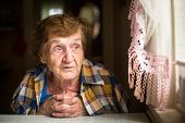 stock photo of loneliness  - Old lonely woman sitting at a table near the window in his house - JPG