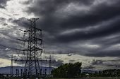 stock photo of power transmission lines  - Power plant transmission line against dark ominous clouds - JPG