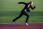 foto of race track  - business woman in start position ready to run and sprint on athletics racing track - JPG