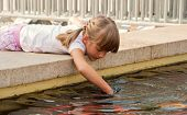 image of game-fish  - Cute little girl with pigtails near a pond with fish - JPG