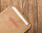 stock photo of top-secret  - Open yellow envelope with top secret stamp and papers on wooden table clipping path - JPG