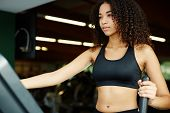 stock photo of time machine  - Beautiful afro american woman with curly hair exercising in gym on a step simulator machine beautiful and healthy woman enjoying time at gym - JPG