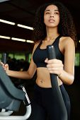 image of cardio exercise  - Attractive young afro american girl with curly hair  exercising on a cardio machine in fitness center - JPG