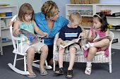 foto of daycare  - Teacher assists preschool boy and girls while they read books during their class - JPG