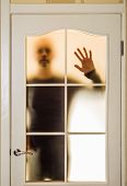 pic of incognito  - Silhouette of an unknown man in black seen through a closed glass door like a ghost or an alien - JPG