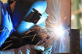 picture of welding  - welder is welding chekered plate with all safety gear in factory