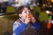 image of hamburger  - Little boy eat hamburger behind glass in fast food restaurant - JPG
